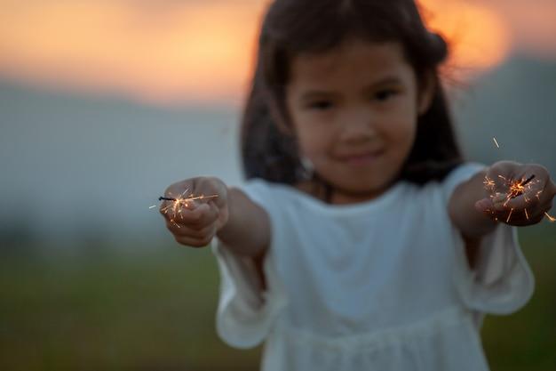 A menina bonito da criança asiática está jogando com os sparklers do fogo no festival no campo do arroz