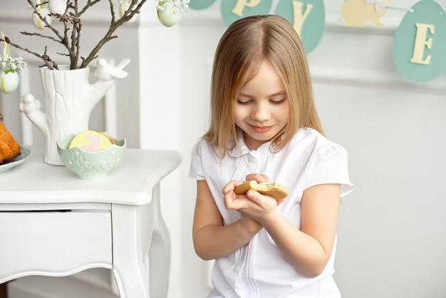 A menina bonito da criança em uma camisa branca está comendo biscoitos