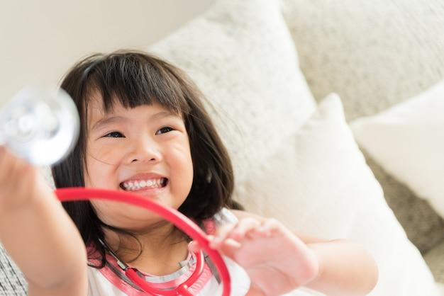 A menina bonito é de sorriso e de jogo o doutor com estetoscópio. criança e saúde conce cuidado