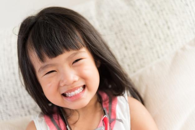 A menina bonito é de sorriso e de jogo o doutor com estetoscópio.