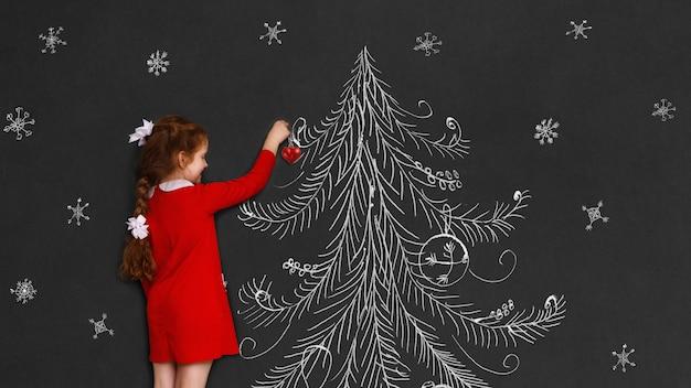 A menina bonito e seu cão do russell do jaque com decoram uma árvore de natal.