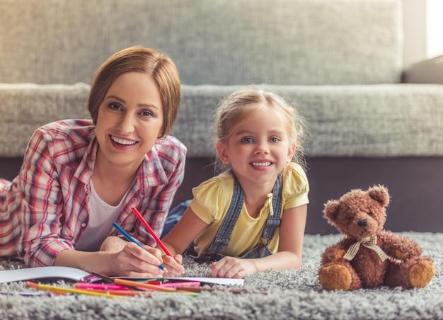 A menina bonito e sua mãe bonita estão desenhando.