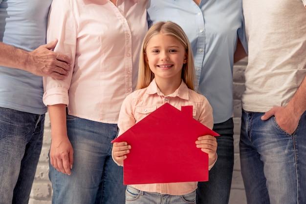 A menina bonito está guardando uma casa de papel que olha a câmera.