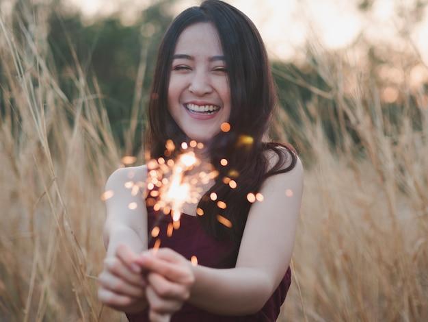 A menina bonito feliz que guarda um chuveirinho no campo de grama seca para comemora.