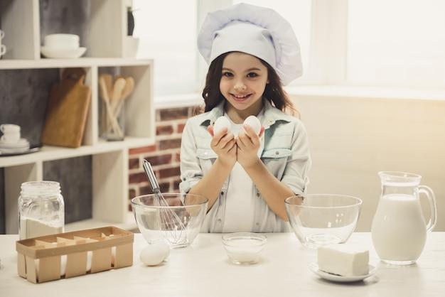 A menina bonito no chapéu do cozinheiro chefe está guardando ovos.