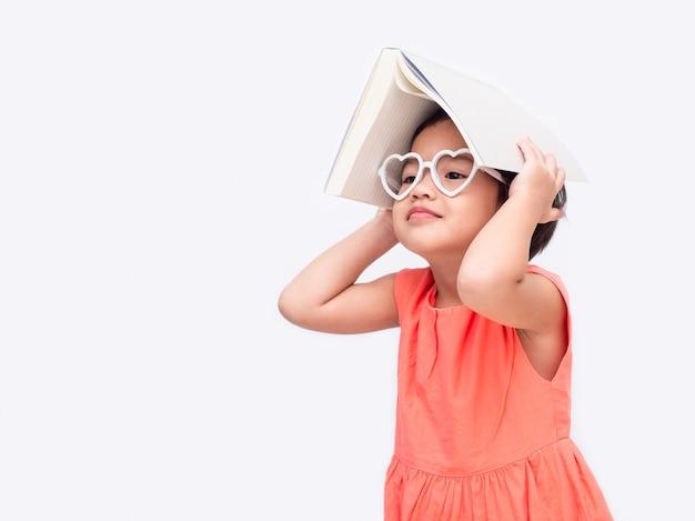 A menina bonito pequena asiática que veste vidros e põe o livro sobre a cabeça.