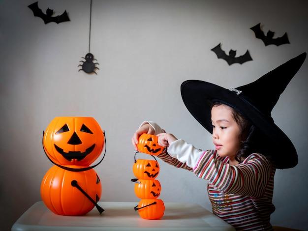 A menina bonito pequena cosplay como uma bruxa e um jogo empilha as cubetas das abóboras sobre o fundo escuro com aranhas e bastões.