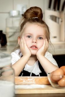 A menina bonito pequena está cozinhando na cozinha. se divertindo enquanto faz bolos e biscoitos ..