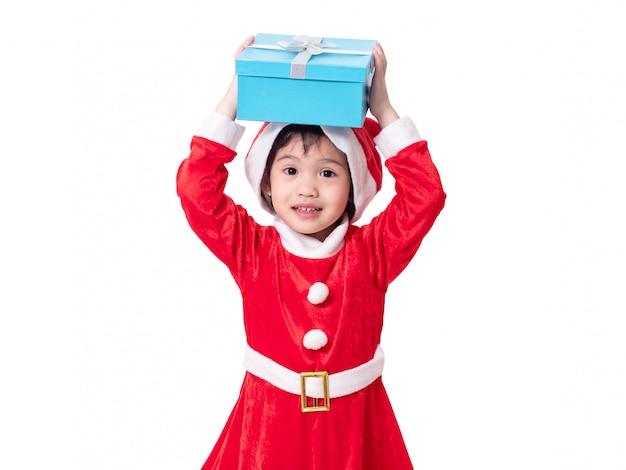A menina bonito pequena vestida como papai noel e põr a caixa de presente azul na cabeça isolada no fundo branco com trajeto de grampeamento.