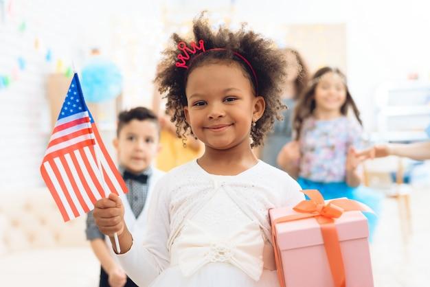 A menina bonito prende um presente e uma bandeira dos eua.