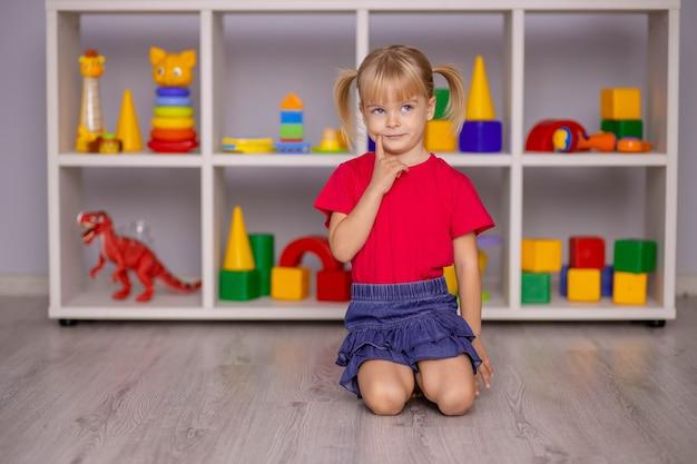 A menina brinca com brinquedos em casa, no jardim de infância ou no berçário. desenvolvimento infantil.