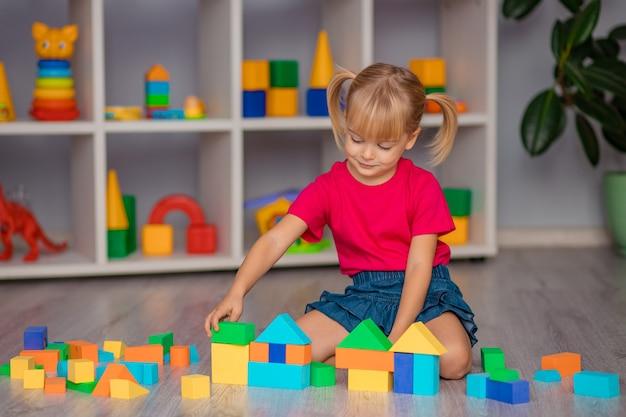 A menina brinca com brinquedos em casa, no jardim de infância ou no berçário.