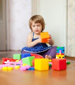 A menina brinca com brinquedos em casa