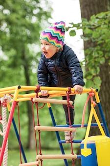 A menina brincando no playground ao ar livre