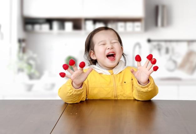 A menina brincava com framboesas nos dedos