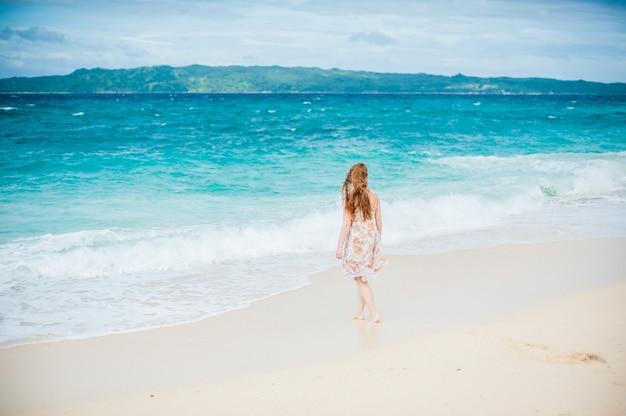 A menina caminha à beira da água no boracay