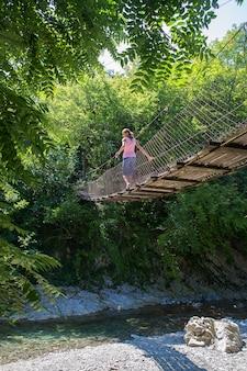 A menina caminha ao longo de uma ponte suspensa entre a floresta acima do rio da montanha