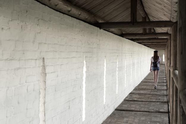 A menina caminha ao longo do corredor longo do mosteiro no contexto de uma parede branca.