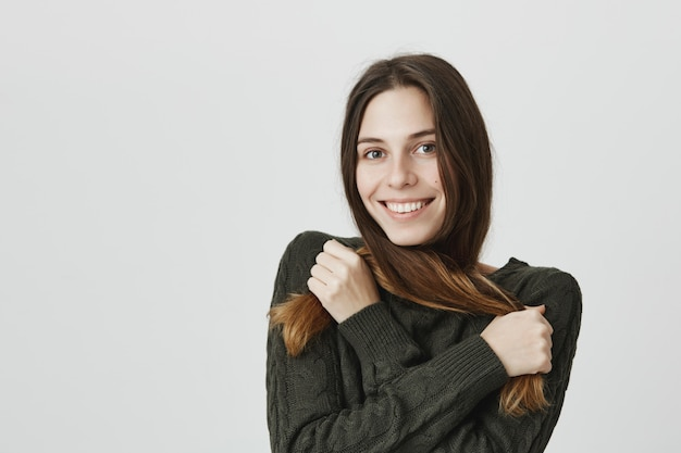 A menina caucasiano de sorriso bonito e macia amarra os fios do cabelo sobre o pescoço