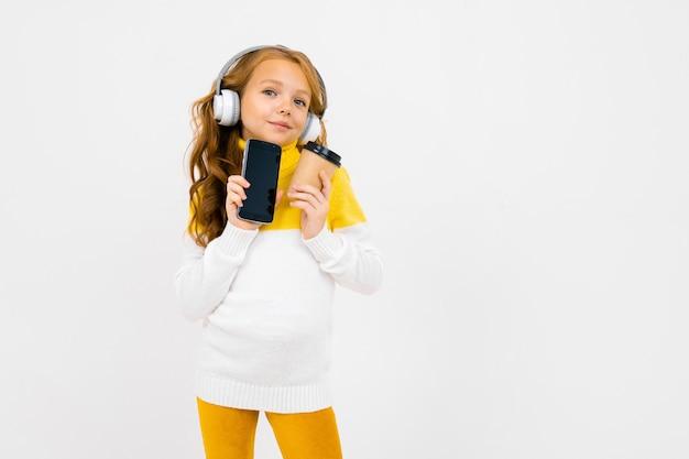 A menina caucasiano do adolescente bonito ouve música com fones de ouvido grandes e bebe o café isolado no branco