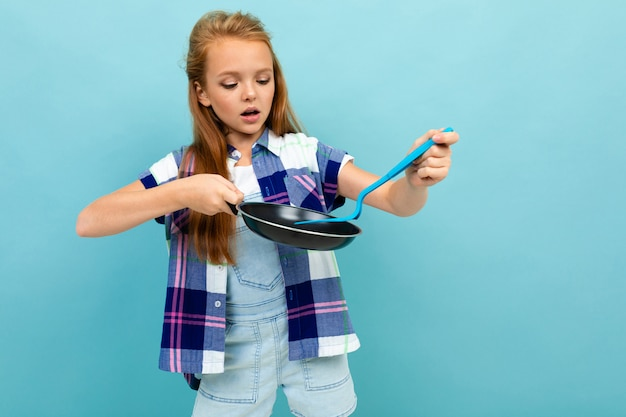 A menina caucasiano do adolescente está indo fritar algo com uma panela isolada no fundo azul