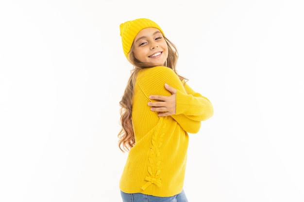 A menina caucasiano feliz no chapéu amarelo e nos hoodies basks isolados no fundo branco