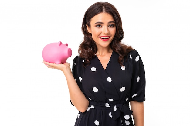 A menina caucasiano nova com sorriso encantador, no vestido preto e branco nas ervilhas prende um mealheiro do porco cor-de-rosa, quadro isolado no branco
