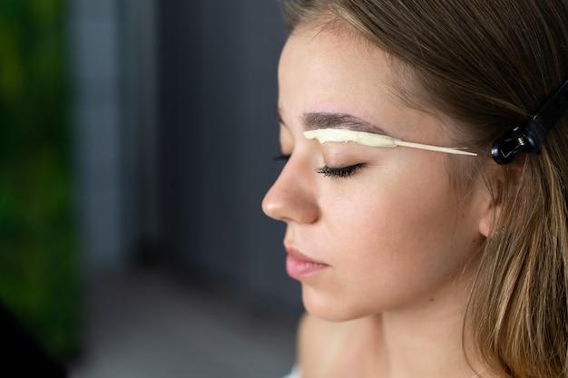 A menina caucasiano nova do esteticista prende a correção da sobrancelha modelo