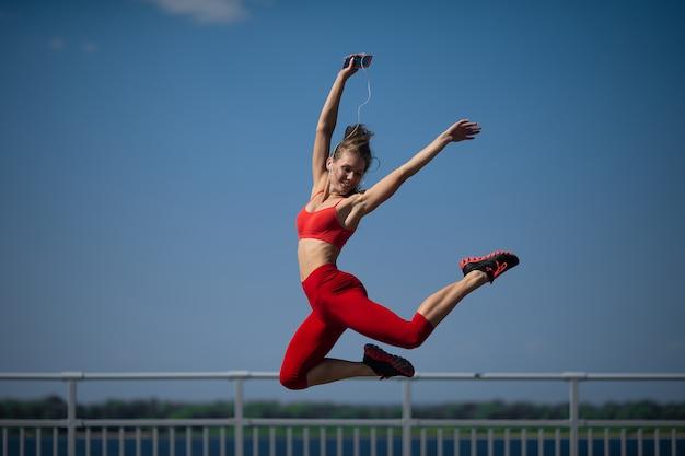 A menina caucasiano nova executa a guita que salta no backround do céu.