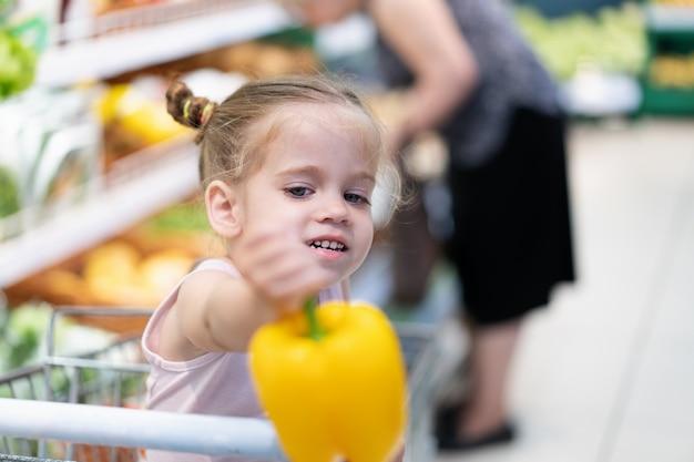 A menina caucasiano pequena escolhe legumes frescos no supermercado.