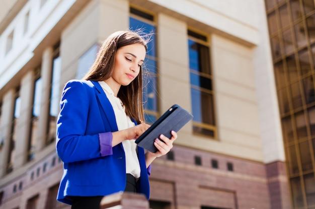 A menina checa seu tablet de pé na rua