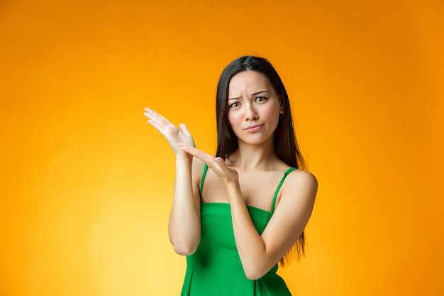 A menina chinesa de pensamento sobre fundo amarelo
