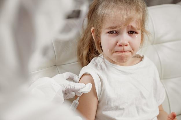 A menina chora magoada e assustada. injeção durante a doença. vacinação.