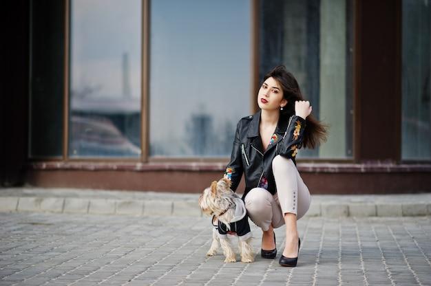 A menina cigana moreno com o cão do yorkshire terrier levantou contra a casa das grandes janelas. modelo de desgaste na jaqueta de couro com ornamentos, calças e sapatos de salto alto.