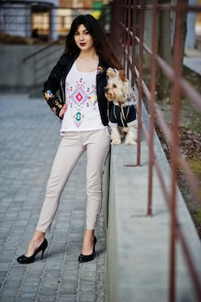 A menina cigana moreno com o cão do yorkshire terrier levantou contra os trilhos de aço. modelo de desgaste na jaqueta de couro com ornamentos, calças e sapatos de salto alto.