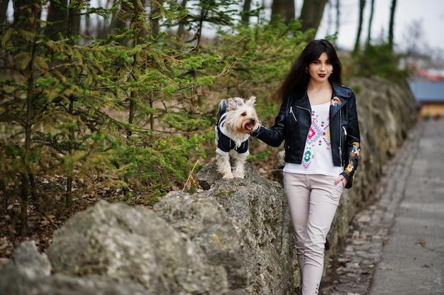 A menina cigana moreno com o cão do yorkshire terrier levantou contra pedras no parque. modelo de desgaste na jaqueta de couro com ornamentos, calças e sapatos de salto alto.