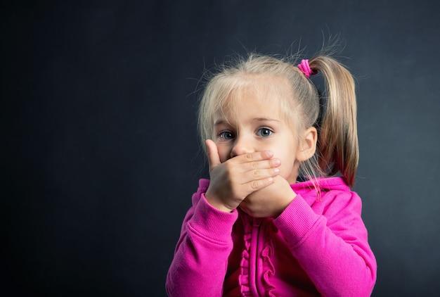 A menina cobre a boca com as mãos