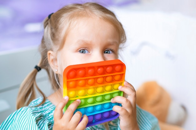 A menina cobre o rosto. a menina brinca com o brinquedo sensorial pop-lo. alívio do estresse e ansiedade. jogo de silicone moderno para crianças estressadas