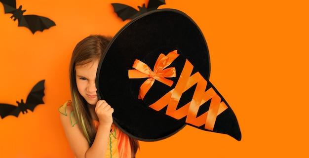 A menina cobre um olho com um chapéu de bruxa com um rosto astuto e sinistro escondendo um sorriso