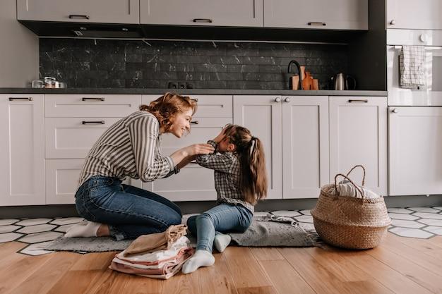 A menina cobriu os olhos enquanto brincava com sua amada mãe na cozinha.