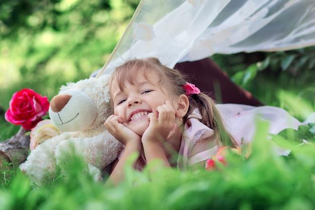 A menina coloca deitado ao ar livre com um ursinho de pelúcia e ri