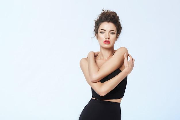 A menina com brilhante compõe no roupa interior retro preto que levanta sobre o espaço azul da cópia da parede.