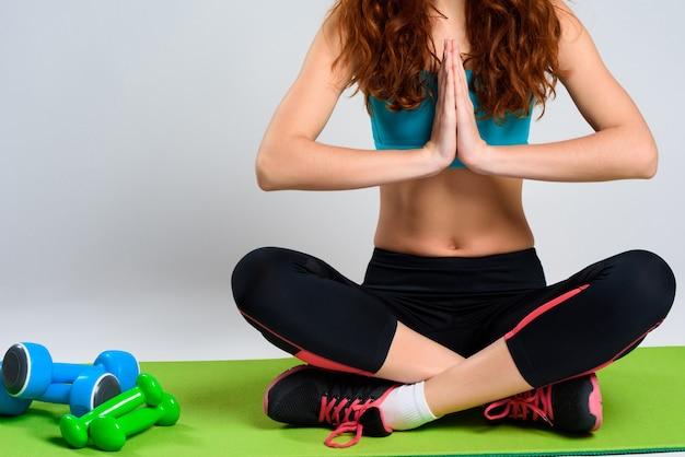 A menina com cabelo encaracolado medita no tapete do gym.