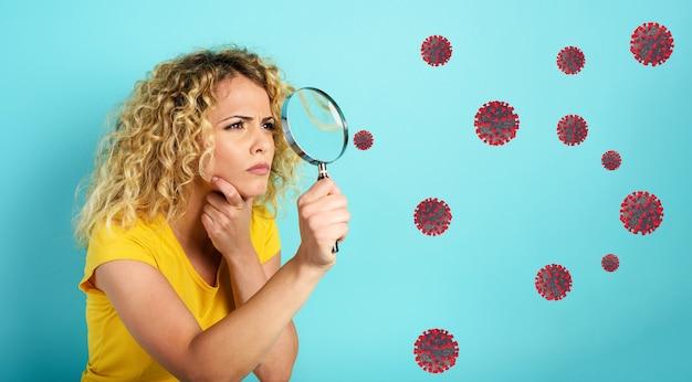 A menina com lente de aumento desconfia do vírus no ar. fundo ciano