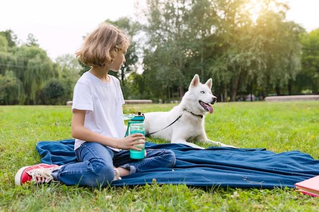 A menina com um cão no parque senta-se na grama