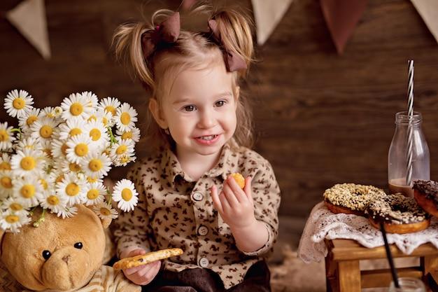 A menina come biscoitos e os alimenta com um ursinho de pelúcia.