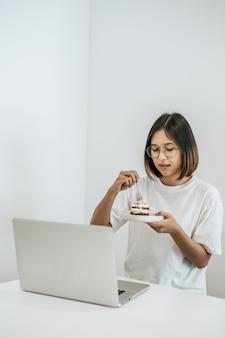A menina come bolo e tem um laptop na mesa.