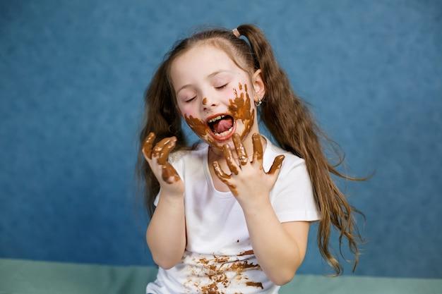 A menina come chocolate e mancha sua camiseta branca, rosto e entrega a ele