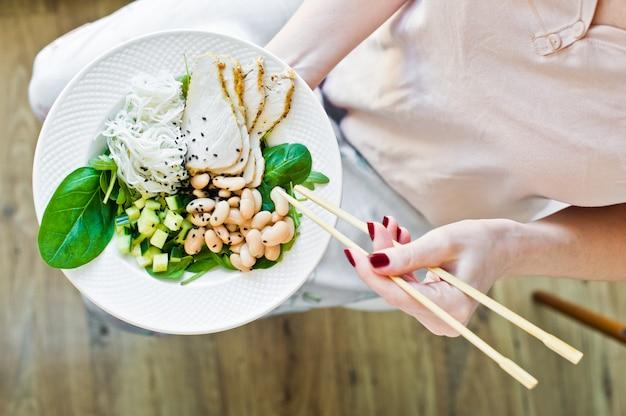 A menina come comida equilibrada saudável, salada com macarrão de vidro, feijão, peito de frango, espinafre, rúcula e pepino