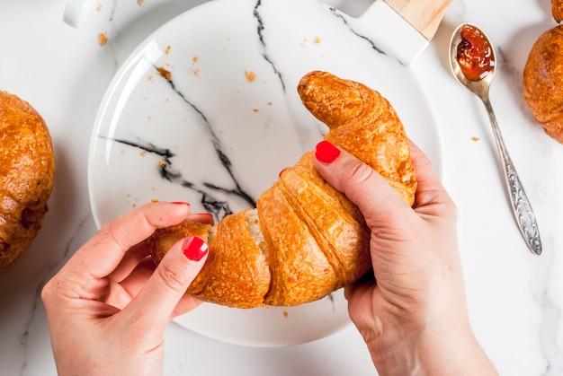 A menina come o café da manhã continental caseiro, croissants, café